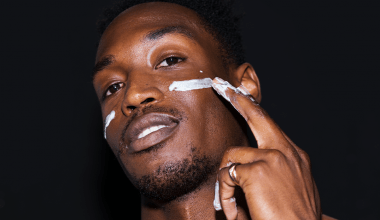 A handsome man puts on face cream as part of his simple skincare routine for men
