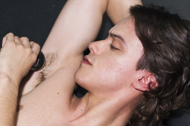 Long haired man applies deodorant to his hairy armpit