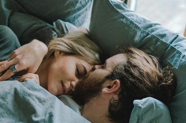 Bearded man and woman cuddling in bed before starting the day.