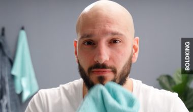 Handsome bald man admiring his freshly shaved head – how to shave your head